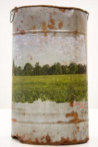Löydetty sarjan teos kultturin piirit ja valokuva metsän reunustamasta pellosta.